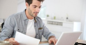 young-man-at-home-office-white-laptop-holding-paper-desk_573x300